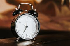 Retro alarm clock on a table. Photo in retro color image style stock photography