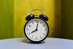 Retro alarm clock on table with vintage background Stock Photography