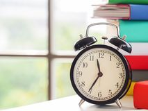 Retro Alarm clock on text books near the window, sunny day in the home office. Lifestyle Concept royalty free stock photo