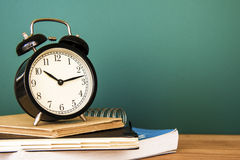 Retro Alarm clock on text books Royalty Free Stock Photos