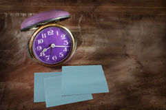 Retro alarm clock and three sticky notes on wooden table Stock Photos