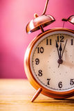 Retro alarm clock with two minutes to midnight. Filtered photo in vibrant colors 50s to 60s. Pink background Stock Photos