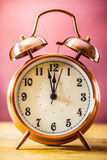 Retro alarm clock with two minutes to midnight. Filtered photo in vibrant colors 50s to 60s. Pink background Royalty Free Stock Photo