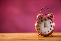 Retro alarm clock with two minutes to midnight. Filtered photo in vibrant colors 50s to 60s. Pink background.  Royalty Free Stock Image