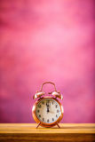 Retro alarm clock with two minutes to midnight. Filtered photo in vibrant colors 50s to 60s. Pink background Stock Photo