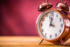 Retro alarm clock with two minutes to midnight. Filtered photo in vibrant colors 50s to 60s. Pink background Stock Image
