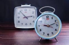 Retro alarm clock on wooden board background Stock Image