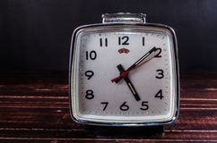 Retro alarm clock on wooden board background Royalty Free Stock Image