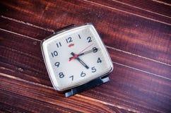 Retro alarm clock on wooden board background Stock Photo