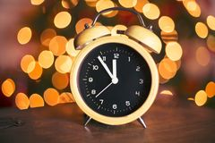 Vintage alarm clock festive countdown. Retro alarm clock on a wooden table bokeh light in background countdown five minutes to midnight Royalty Free Stock Photos
