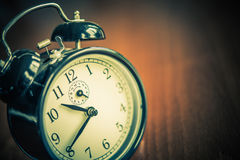 Retro alarm clock on wooden table. Time concept. Stock Images