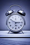Retro alarm clock on wooden table Stock Images