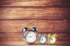 Retro alarm clocks on a table. Stock Photos
