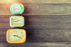 Retro alarm clocks on wood table. Retro or vintage color filtere Royalty Free Stock Photos