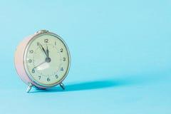 Retro alarm-klok tijd op blauwe pastelkleurachtergrond royalty-vrije stock fotografie