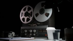 Retro analog quarter inch tape recorder being operated in a darkened room. Atmospheric film noir style shots of an analog quarter inch tape recorder being stock video footage