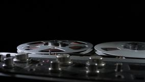 Retro analog quarter inch tape recorder being operated in a darkened room. Atmospheric film noir style shots of an analog quarter inch tape recorder being stock video