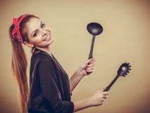 Retro- angeredete Frau, die Spaß mit Küchenzubehör hat Lizenzfreie Stockbilder