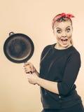 Retro- angeredete Frau, die Spaß mit Küchenzubehör hat Stockfotos
