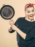 Retro- angeredete Frau, die Spaß mit Küchenzubehör hat Stockfotografie