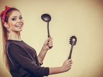 Retro- angeredete Frau, die Spaß mit Küchenzubehör hat Stockbilder