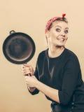 Retro- angeredete Frau, die Spaß mit Küchenzubehör hat Lizenzfreies Stockfoto