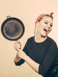 Retro- angeredete Frau, die Spaß mit Küchenzubehör hat Lizenzfreie Stockfotos