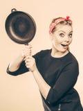Retro- angeredete Frau, die Spaß mit Küchenzubehör hat Lizenzfreie Stockfotografie