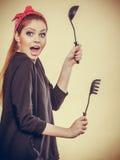 Retro- angeredete Frau, die Spaß mit Küchenzubehör hat Stockfoto