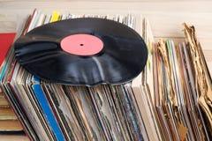 Retro- angeredetes Bild einer Sammlung alten Vinylaufzeichnungs-Langspielplatten-` s mit Ärmeln auf einem hölzernen Hintergrund G Stockbilder
