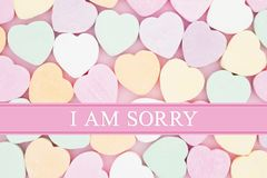 Retro apology message with candy hearts. Retro apology message, Retro heart shaped candy on pick fabric with text I am sorry Royalty Free Stock Photos