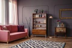 Retro armadietto di legno con i libri e le decorazioni che stanno in dar fotografia stock libera da diritti