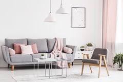Retro armchair, grey sofa with pink pillows and coffee tables in stock photography