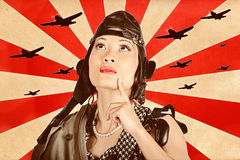 Retro asian pinup girl. War planes of revolution. Retro propaganda take-off. Asian pinup freedom fighter looking up to the skies of revolution to scout the war Stock Image