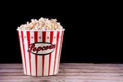 Retro ask för popcorn fullt ut på det trälantliga skrivbordet royaltyfria foton