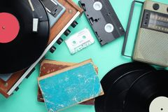 Retro attributes, 80s media. Vinyl player, video cassettes, audio cassettes, records, radio, old books on blue background. Top view stock image