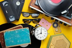 Retro attributes, 80s media. Vinyl player, video cassettes, audio cassettes, 3d glasses, records, radio, vintage alarm clock, old books on a yellow background royalty free stock image