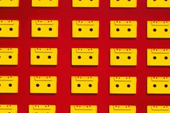 Collection Yellow Audio Cassettes Tapes On Red Background, Top View. Creative Concept Of Retro Technology. Retro audio tape tapes lie on a red background royalty free stock photos