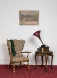 Retro- aufwändiger Lehnsessel, alter Plattenspieler, Zylinder auf rundem Couchtisch Lizenzfreie Stockfotos