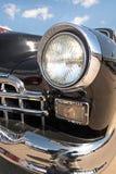 Retro- Auto des Scheinwerfers auf Hintergrund des bewölkten Himmels weinlese (Luxur Stockbilder