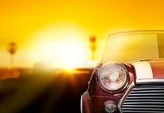 Retro auto hoofdlicht op straat op de zonsondergangachtergrond stock afbeelding
