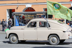 Retro- Auto mit einer Flagge an der festlichen Demonstration Stockfotografie