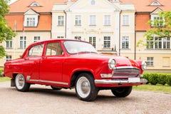 Retro automobile rossa in fonte della villa di festa Immagine Stock Libera da Diritti