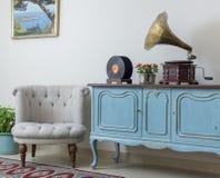 Retro av den vita fåtöljen och tappningträljus - blå serveringsbord Royaltyfri Foto