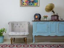 Retro av den vita fåtöljen, tappningträljus - blå serveringsbord, den gamla skivspelaregrammofonen och vinylrekord Royaltyfri Fotografi