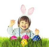 Retro baby Bunny with Easter Eggs. Laughing baby boy with bunny ears, bow tie, suspenders hunting for Easter eggs in a green grass. Retro fashion style. Studio Stock Images
