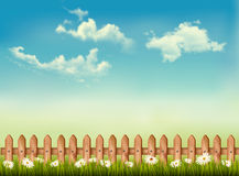 Retro background with a fence, grass, sky and flowers. Royalty Free Stock Images
