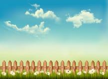 Retro bakgrund med ett staket, ett gräs, en himmel och blommor. Royaltyfria Bilder