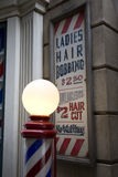 Retro barber shop. Old retro barber shop with signage and prices shoot at dusk with the light post light up royalty free stock photo