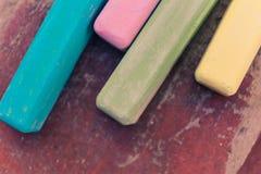 Retro barwioni kredowi kije na starej drewno desce jako kopia interliniują tło obrazy stock